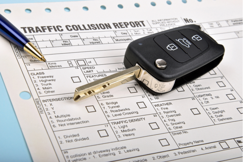 Accident report with key and pen after autonomous car crash