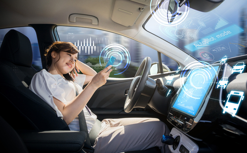 Woman surfs on phone in driver seat of autonomous vehicle