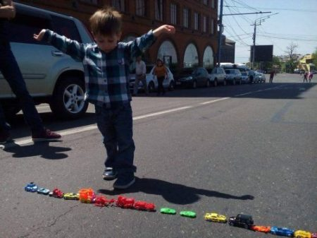 Armenian boy with rainbow colored toy cars blocking traffic