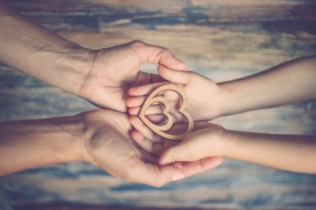Adult hands holding child's hands holding a double heart