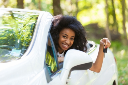 Jubilant black teen holding car keys while sitting in white convertible