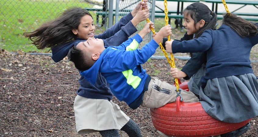 Wesley-Rankin after-school participants play on a swing