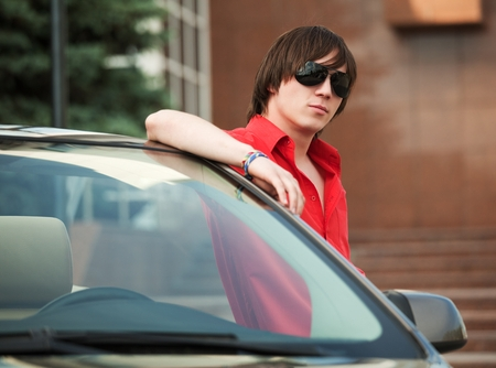 Cool teen stands next to car