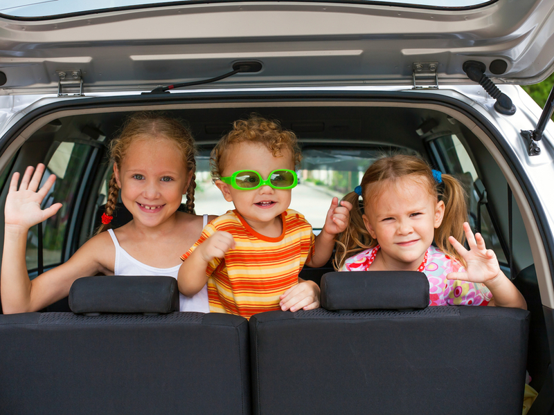 summer family road trip three children in back seat
