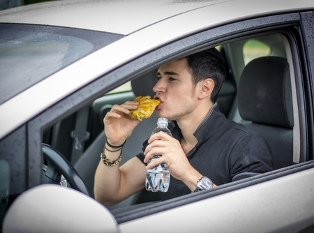 Driver eats and drinks at the wheel